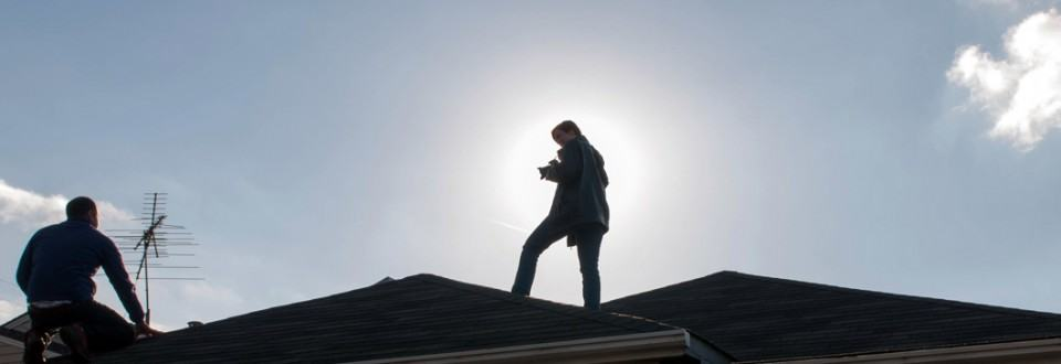 Sallie Goetsch silhouetted on a rooftop in El Cerrito, photographing solar panels.